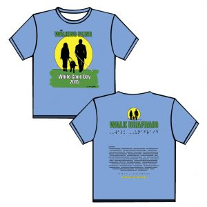 """2015: light blue shirt, black, green, yellow, white ink. FRONT: THE WALKING BLIND in green letters out lined in black are placed above a bright yellow setting sun.  Walking side by side with the sun to their backs are black silhouettes of a woman walking with a guide dog who has glowing yellow eyes and a man using a long white cane. Below is green grass with the phrase in white outlined in black White Cane Day 2015. BACK: smaller image from front of shirt sits above in green letters outlined in black the phrase """"WALK UNAFRAID"""" below the same phrase in puffed Braille.  Moving downward are a list of sponsors, in Braille the phrase """"Ready to work…Ready to Contribute"""" and in yellow print the phrase """"Blind Americans Equality Day"""""""